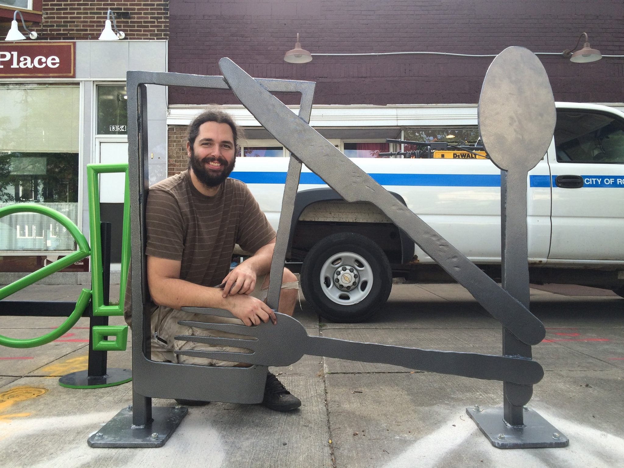 Jesse with his dinnerware bike rack. Located right outside James Brown's Place. Keep up with his other work on Instagram @skillhoarder and @cyrcraftcustoms.[IMAGE: NeighborWorks]